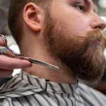 barber holding a pair of scissors ready to trim a customer's beard