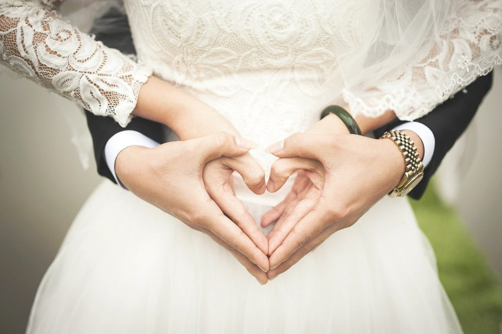half-body shot of a bride's and groom's hands forming a heart together