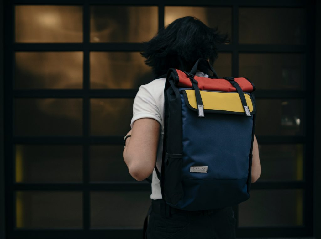 man carrying a navy blue backpack with red and yellow accents