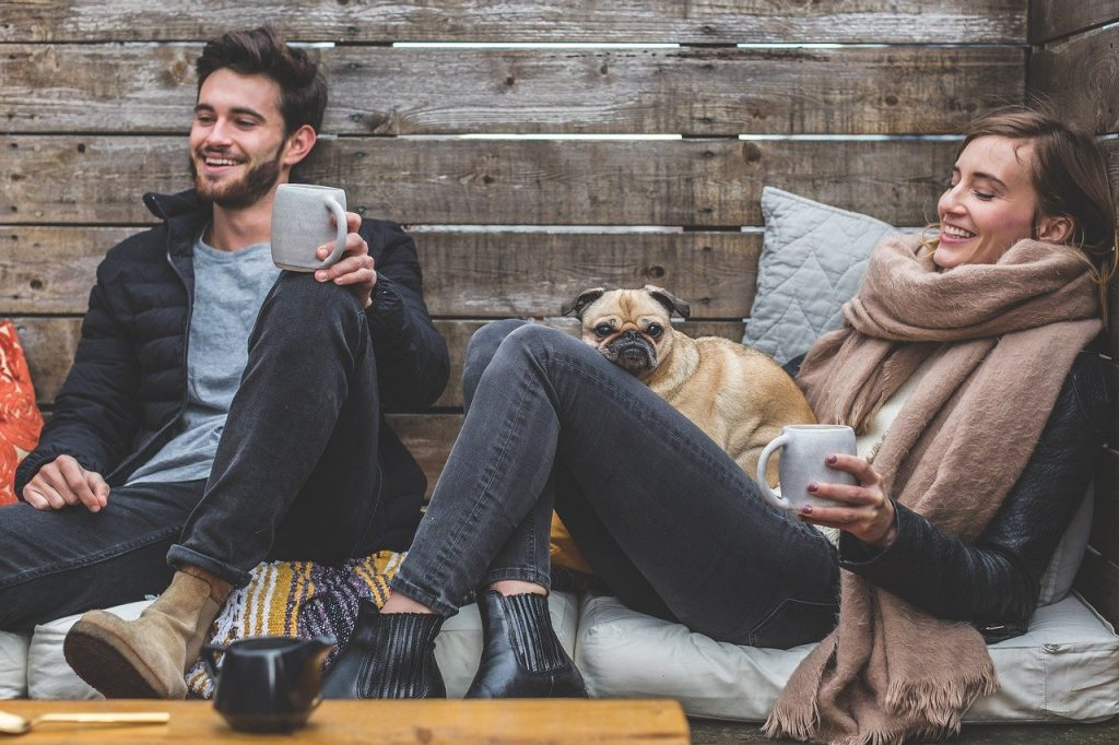 couple seated laughing and smiling together with tea cups and a pug dog