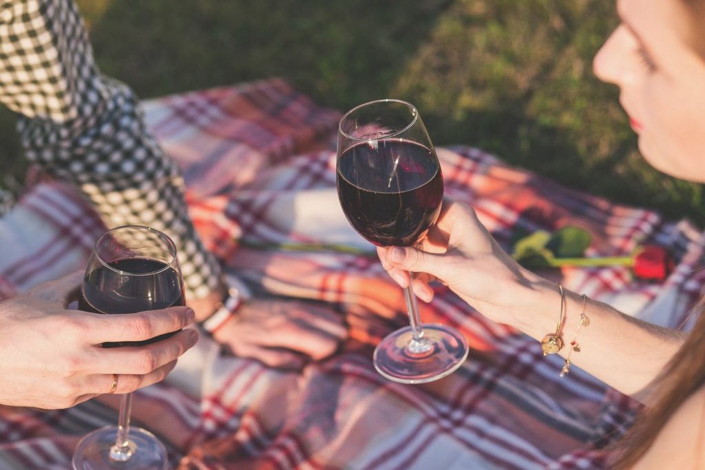couple holding wine glasses on a picnic blanket