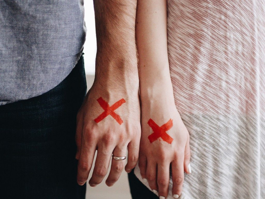 couple's hands side by side with a red X marked on each of them