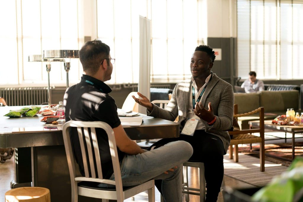 two men sitting at a table and having a discussion
