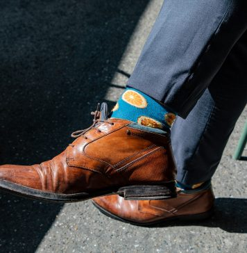 man in suit pants and leather shoes wearing blue socks with oranges on them