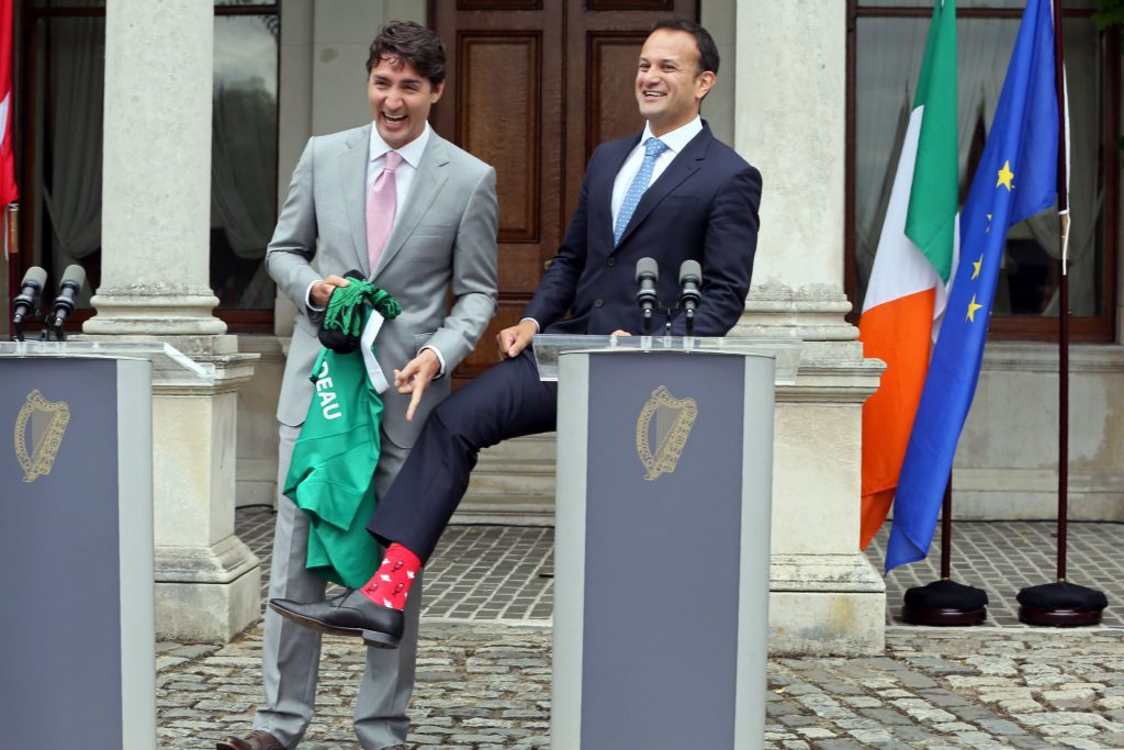 Justin Trudeau laughing and pointing as Irish PM Leo Varadkar shows off his Canadian socks