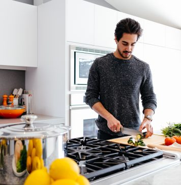 man cutting vegetables near a stove in a white kitchen