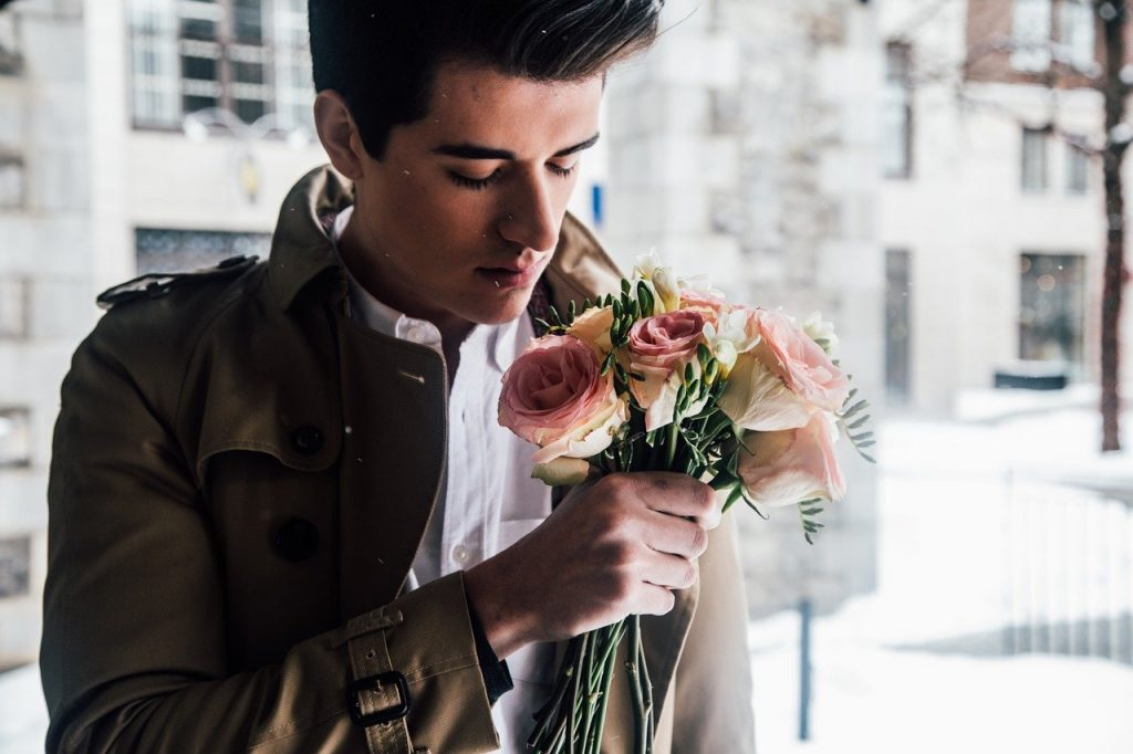 man with a brown coat and white shirt posing with a bouquet of roses near a window