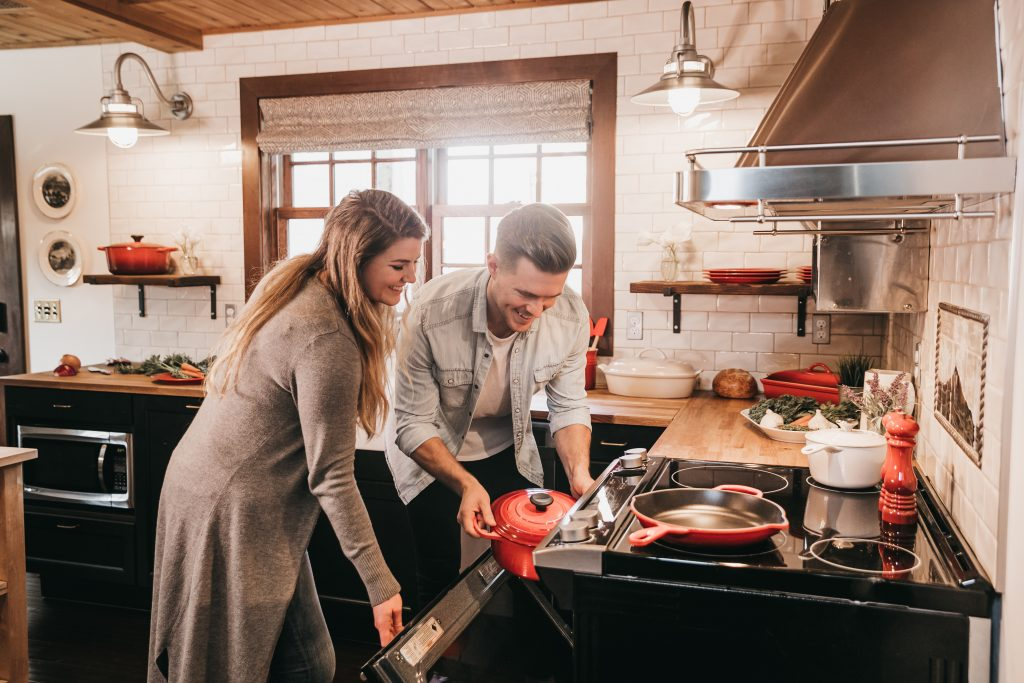 couple smiling and putting a casserole pot in the oven in a home kitchen