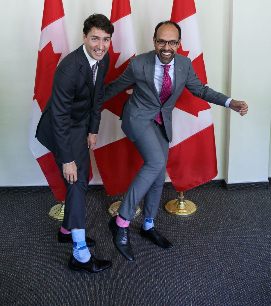 Justin Trudeau showing off his dual colored NATO socks with Staff of the Canadian Joint Delegation to the North Atlantic Council