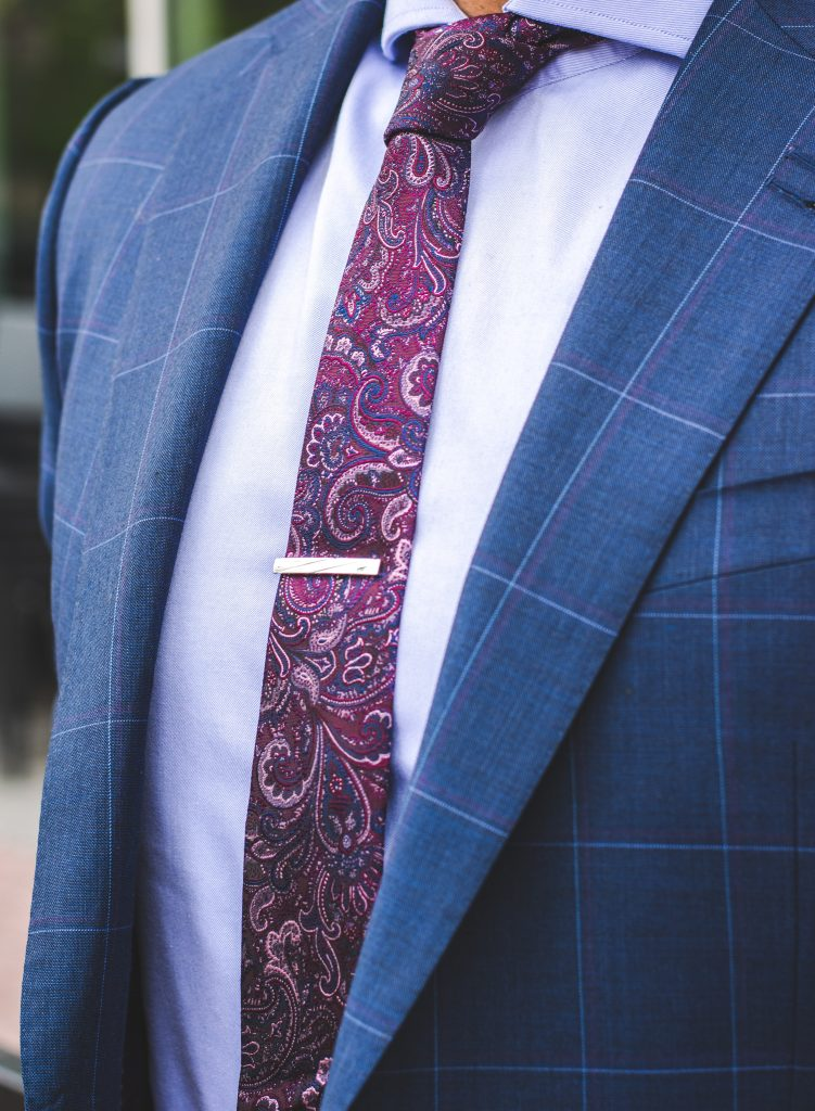 man in a dark blue striped suit with a magenta paisley necktie