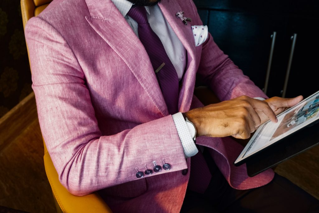 man in a pink suit holding a tablet