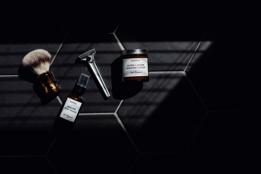 shaving products and tools on a dark, dimly-lit background