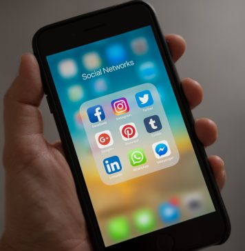 hand holding a smartphone with a folder showing different social media icons