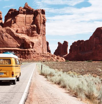 camper van driving on the road in a mountainous desert area