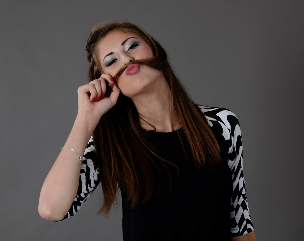 "woman using her hair to create a ""mustache"""