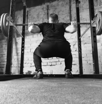 black and white pic of man squatting and lifting a barbell at squat rack in the gym