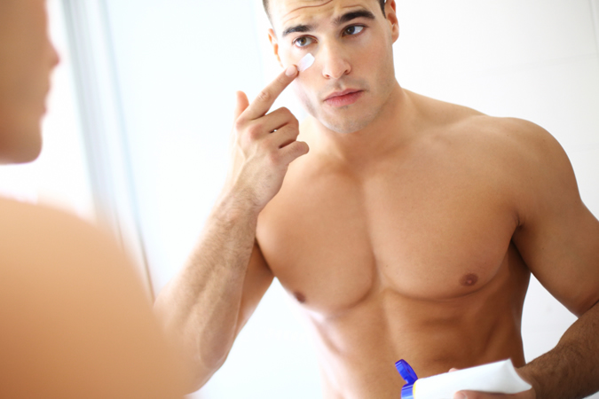 a shirtless man in the bathroom looking in the mirror and applying face cream