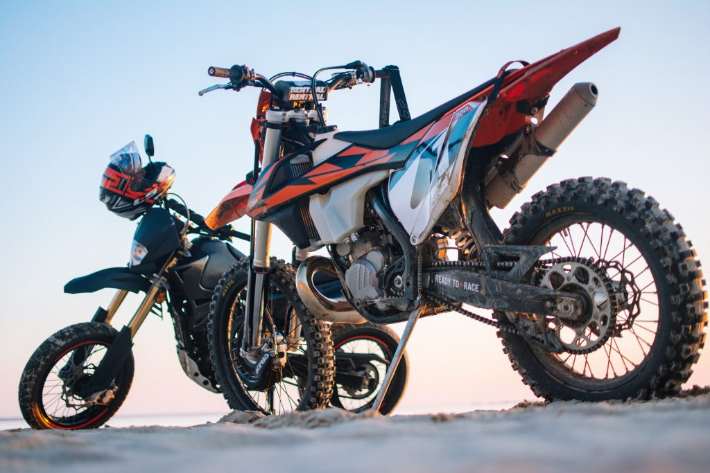 two white-and-orange and black dual-sport motorcycles on rocky ground against the sunset