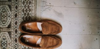 top view of a pair of brown suede penny loafers placed partially on a rug on the floor