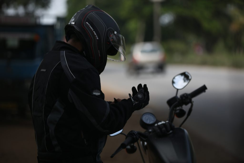 man in full motorcycle gear putting on his gloves while standing near a motorcycle on the side of the road