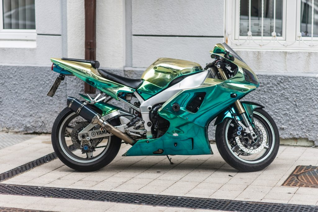 chrome teal sports bike parked on the pavement