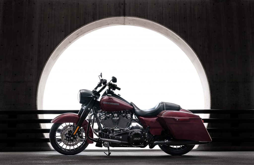 deep red touring motorcycle against a dark wall with a round opening letting in light