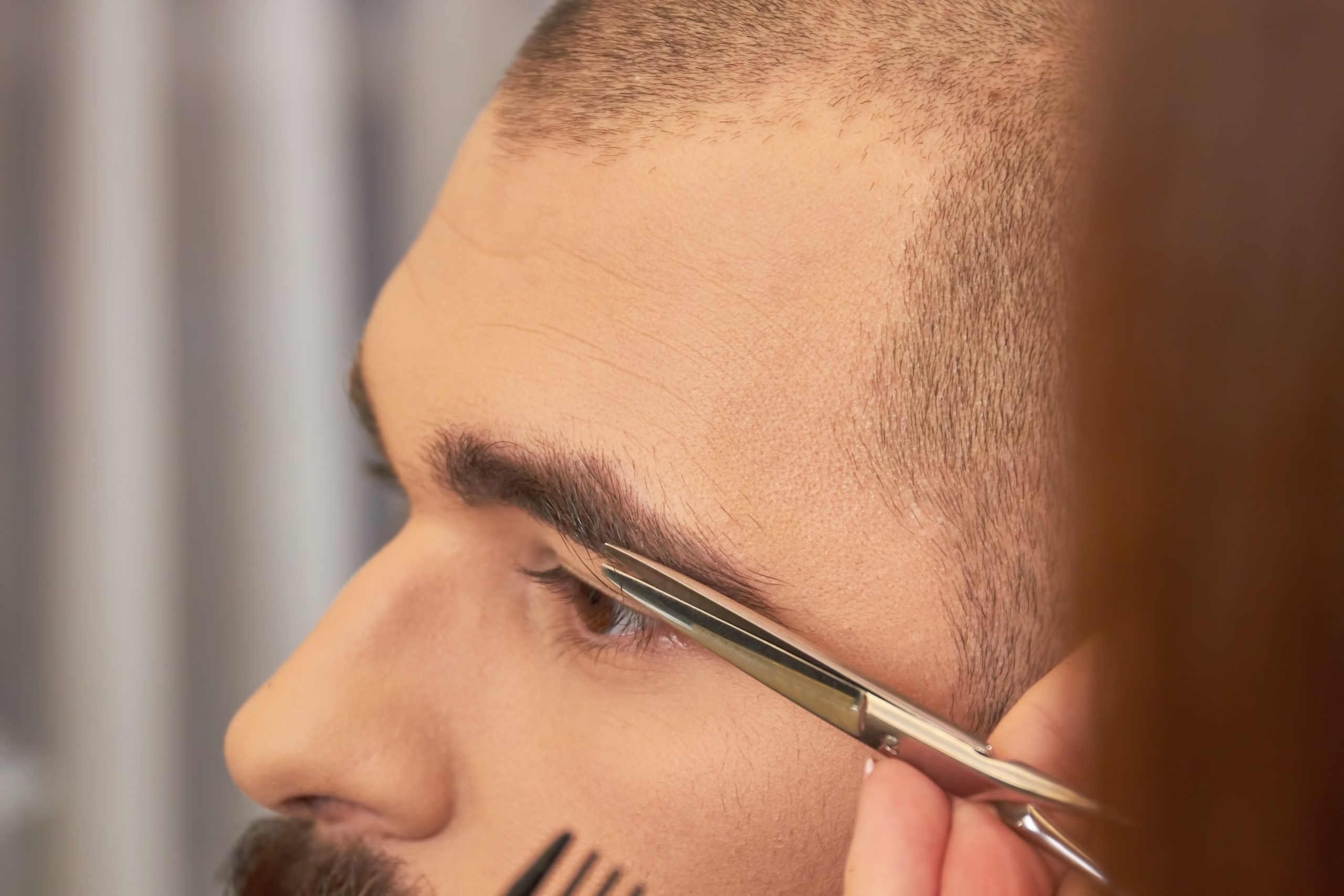 Scissors cutting eyebrow of man. Brow grooming close up.