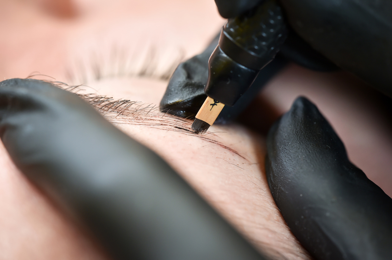 Microblading eyebrows, getting facial care and tattoo at beauty salon