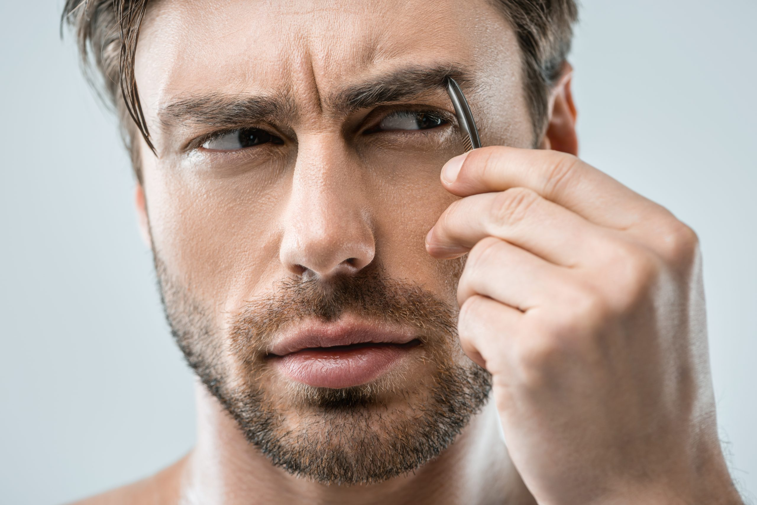 A man plucking his eyebrows with a tweezer.