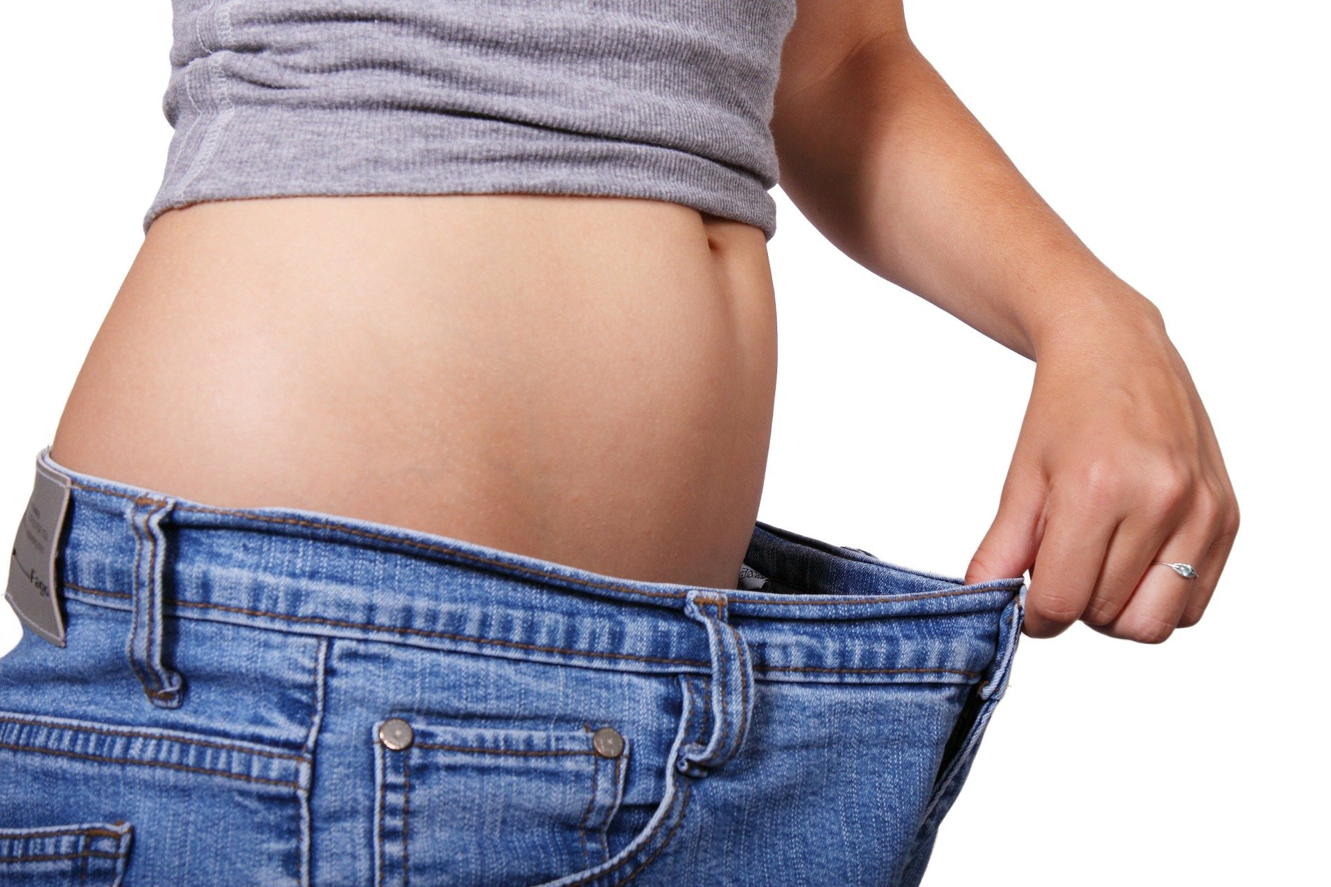 a woman's belly and the waist of her jeans stretched out to show her weight loss