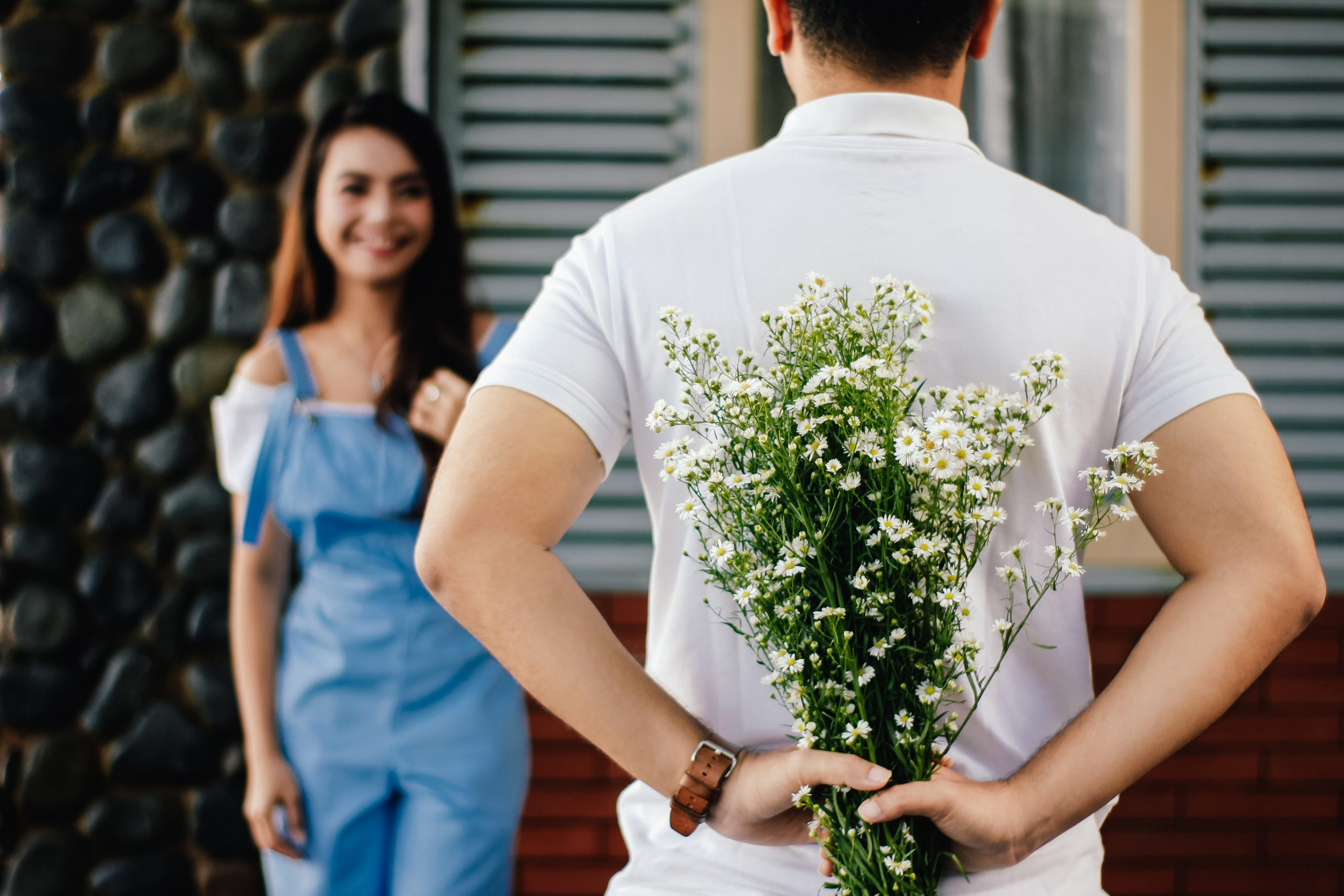 man with his back to the camera and holding a bunch of flowers as he faces a girl smiling in the background