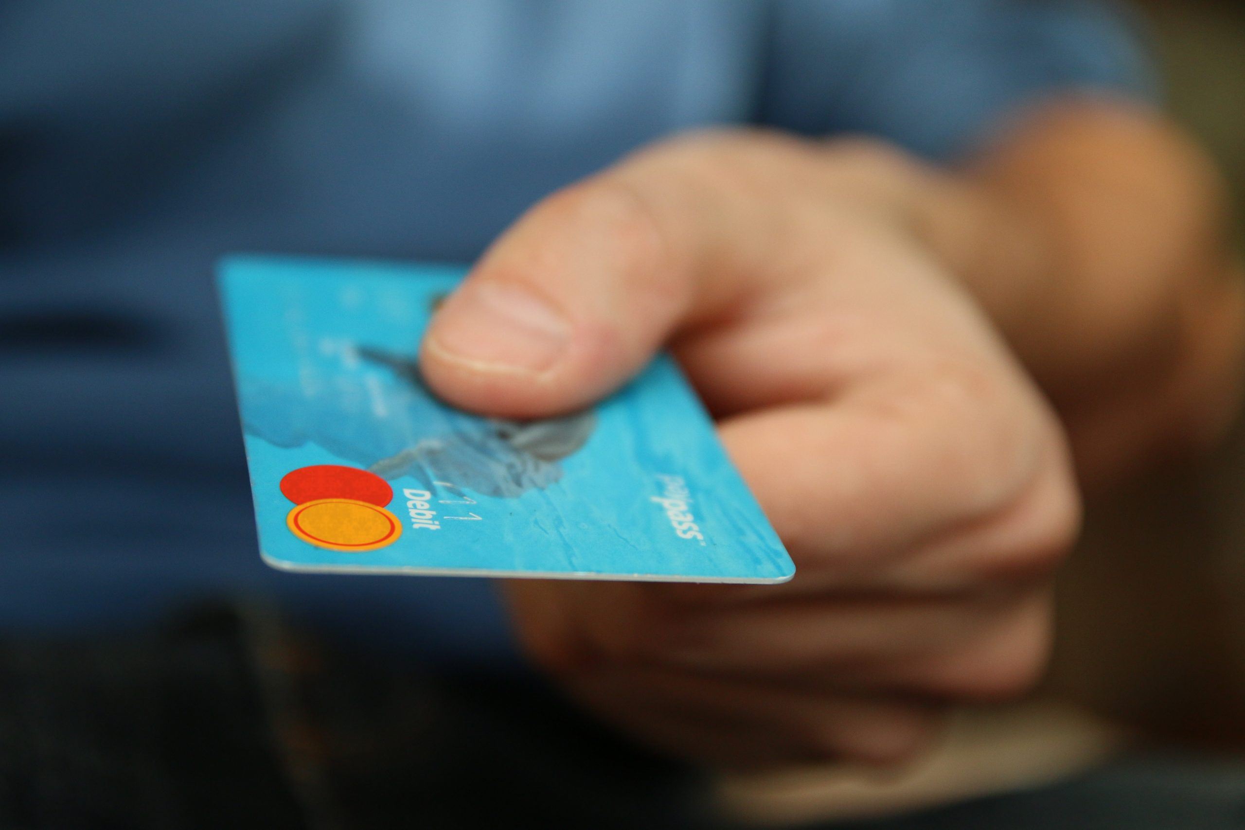 focus shot of man's hand holding out a debit card