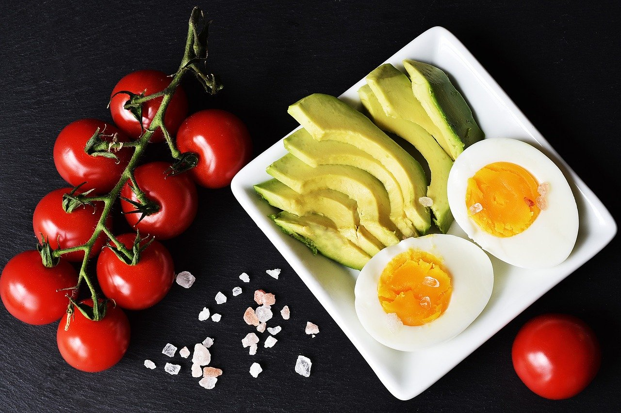 vine tomatoes and himalayan salt against a black background and a plate of sliced avocado and a boiled egg cut in half