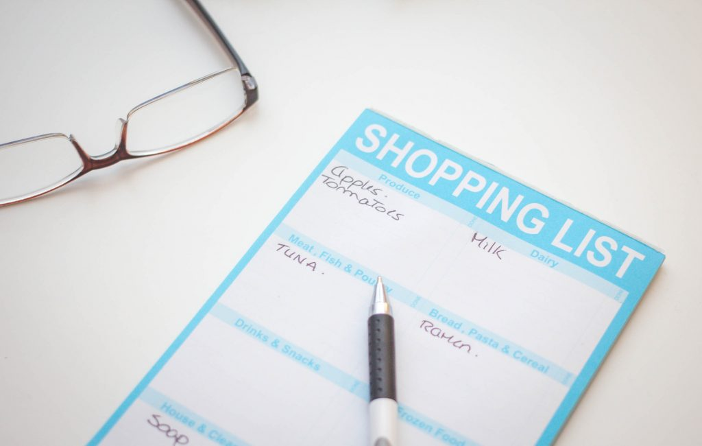 a blue shopping list writing pad and a pen with a pair of black-rimmed eyeglasses in the corner