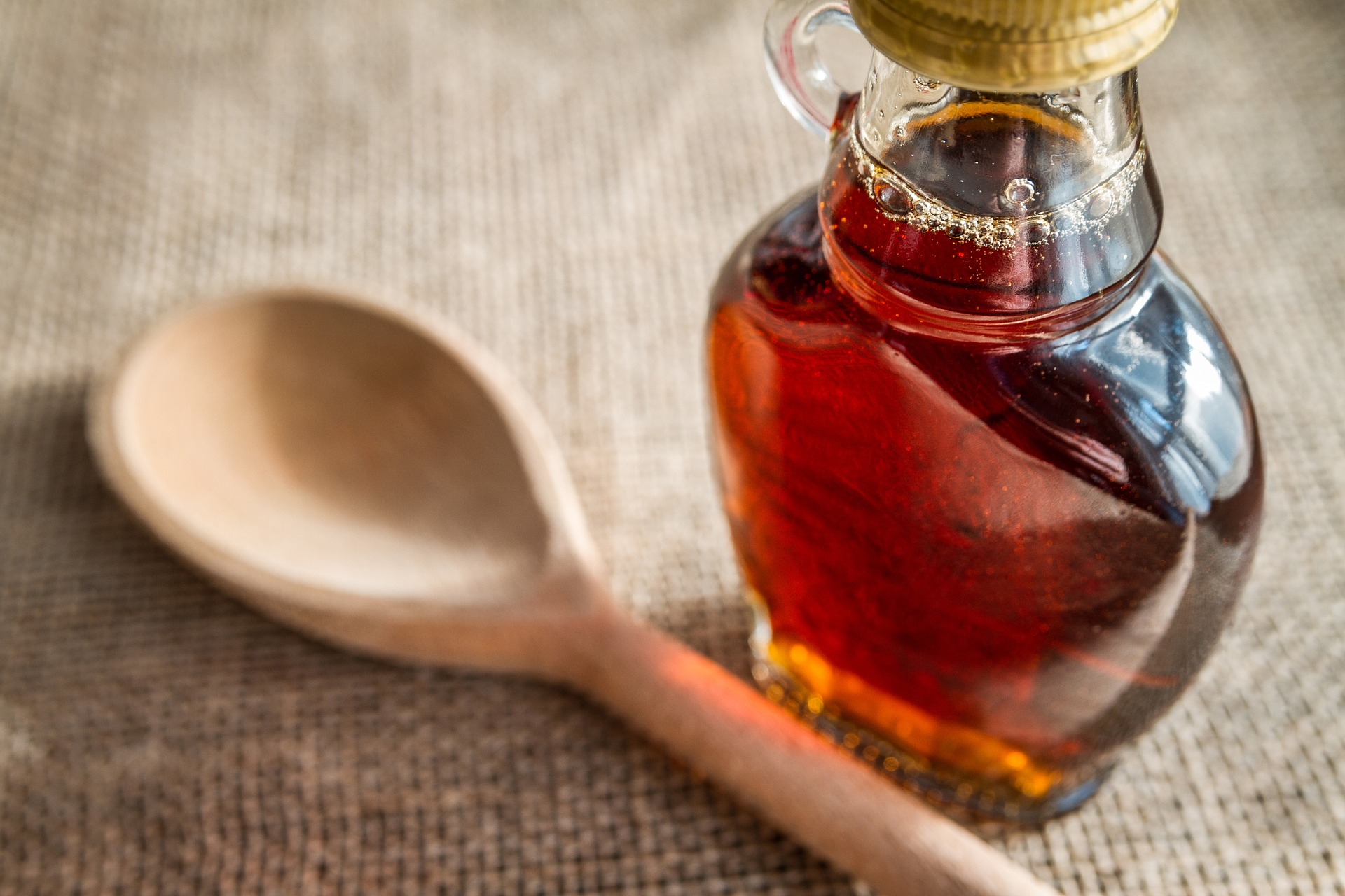 a bottle of maple syrup and a wooden spoon