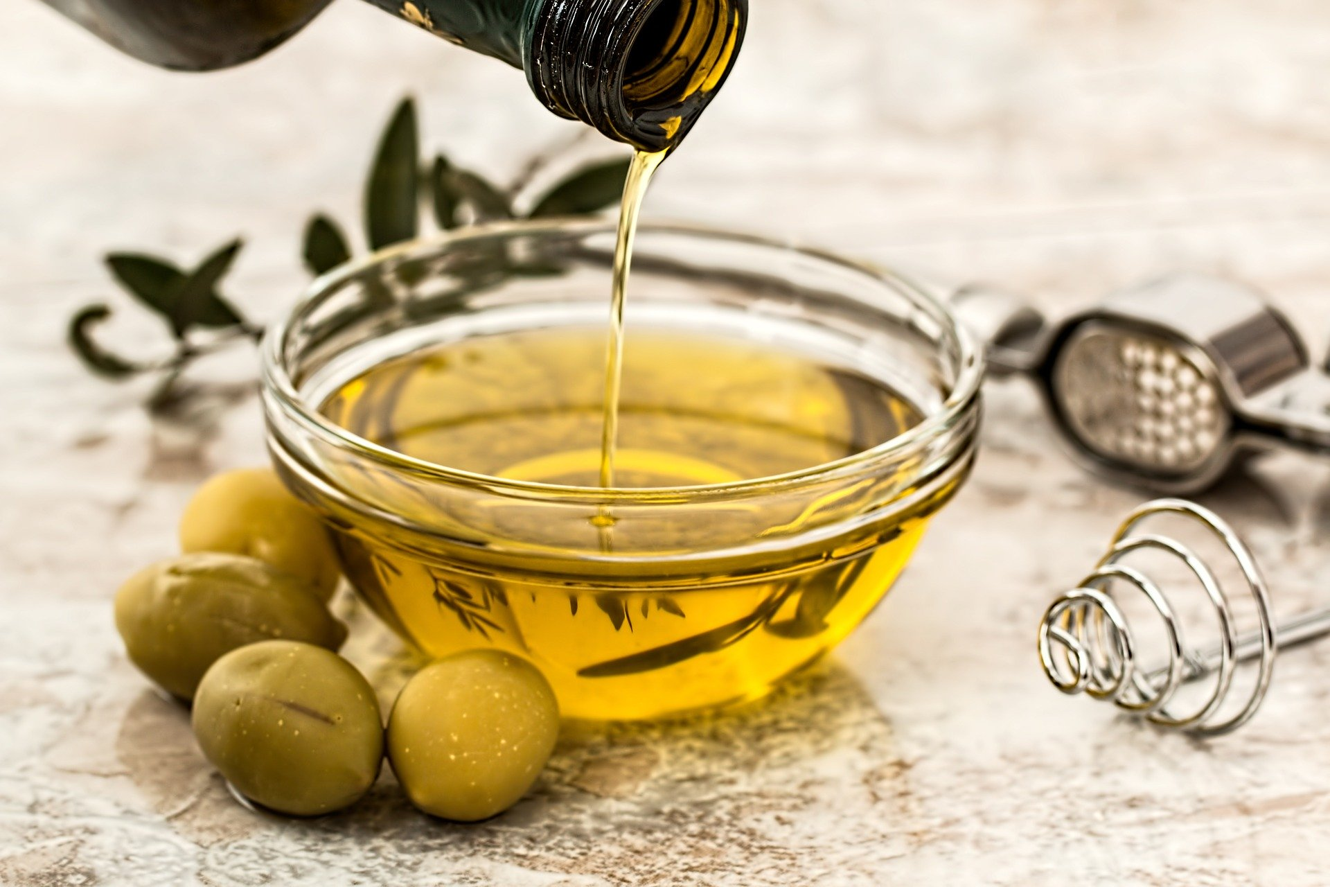 olive oil being pour into a small glass bowl with olive decorations, an extractor and whisk around it