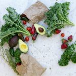 flatlay of various fruits and vegetables with brown paper bags