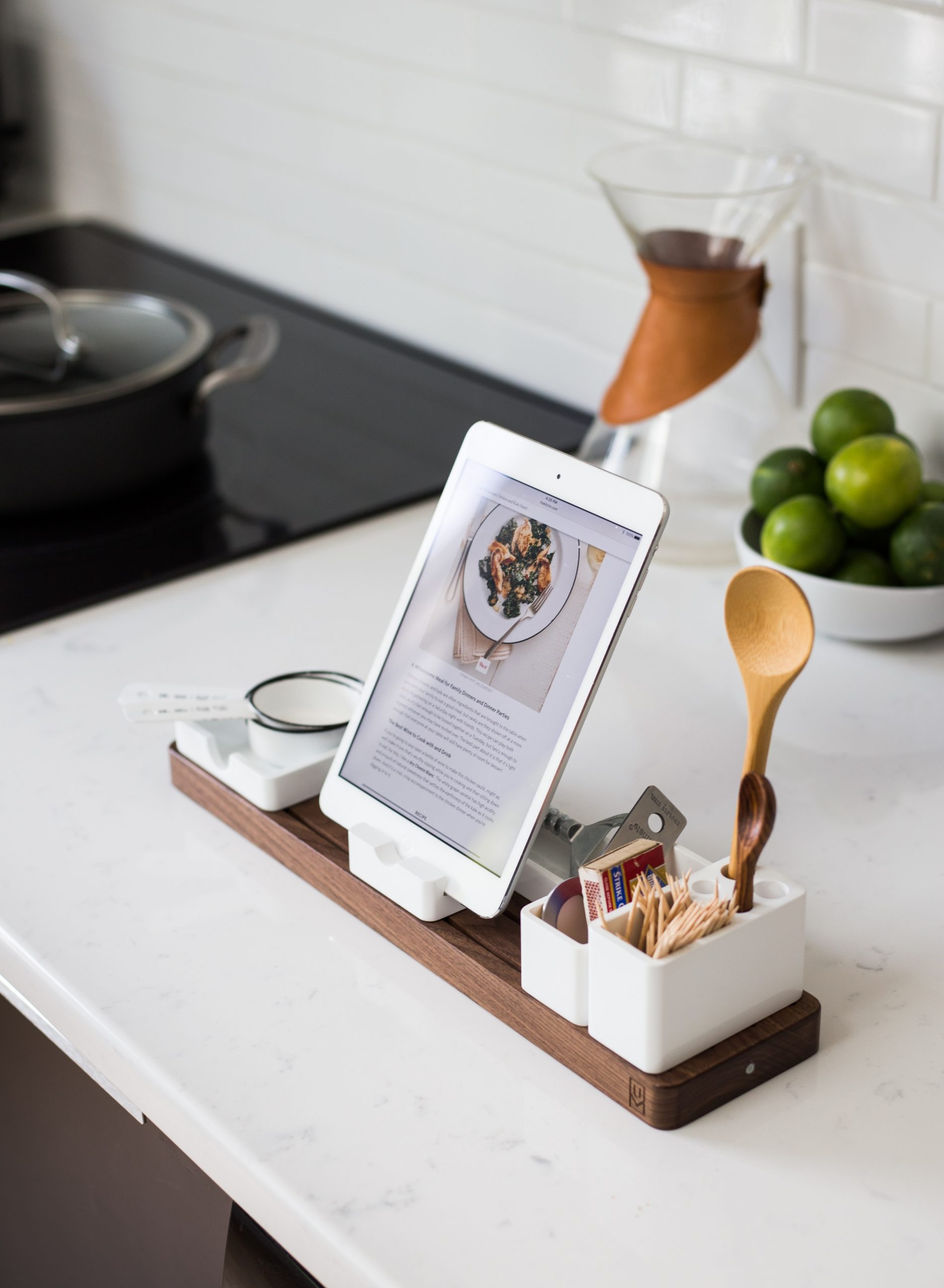 a tablet showing a food website page on a tabletop organizer on the kitchen countertop