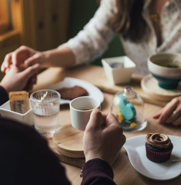 couple holding hands over a table while having dessert and drinks at a cafe