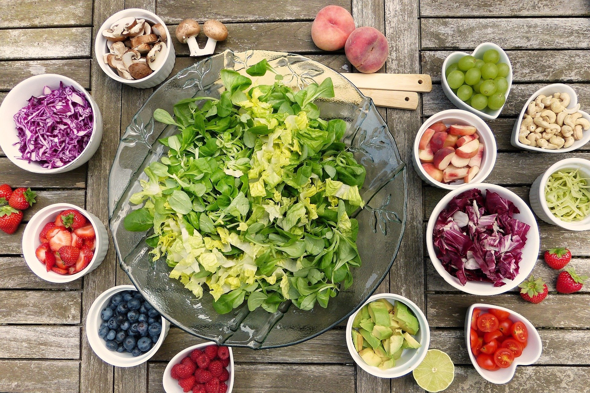 a salad bowl of leafy greens surrounded by other smaller bowls of fruit, other vegetables and nuts