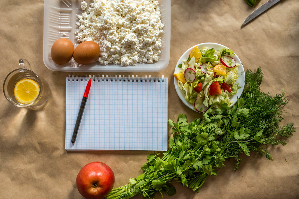 a grid notepad and marker pen surrounded by lemon water, eggs, cauliflower rice, parsley, an apple and salad, intermittent fasting, healthy foods, diet planning