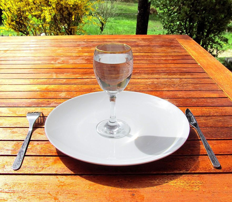 a glass of water on an empty plate with a knife and fork on either side placed on a wooden table outdoors, intermittent fasting, dieting, weight loss