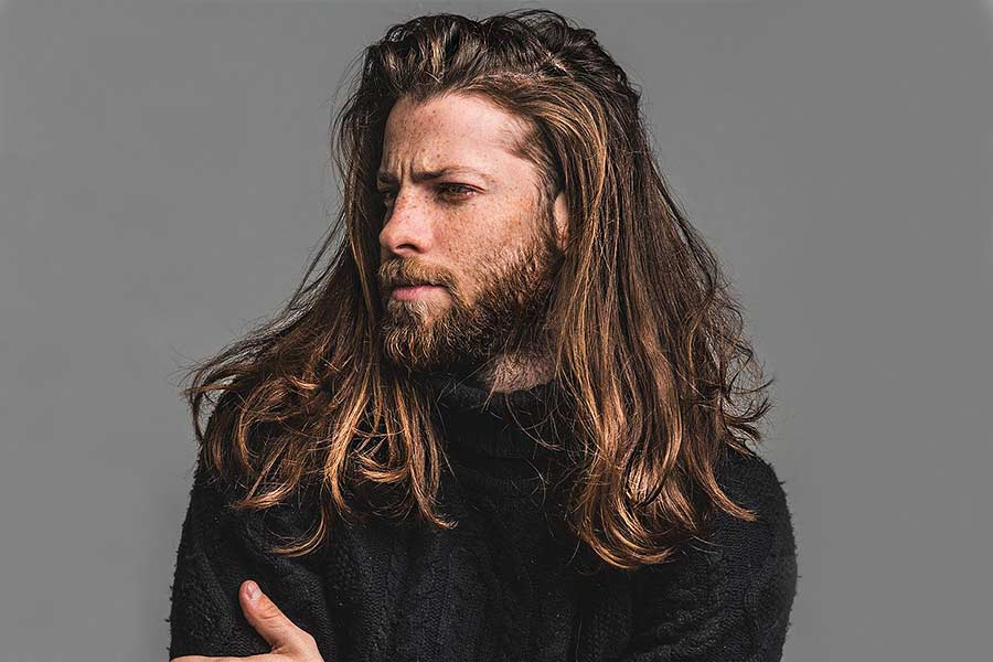 bearded man in a black turtleneck sweater with long hair