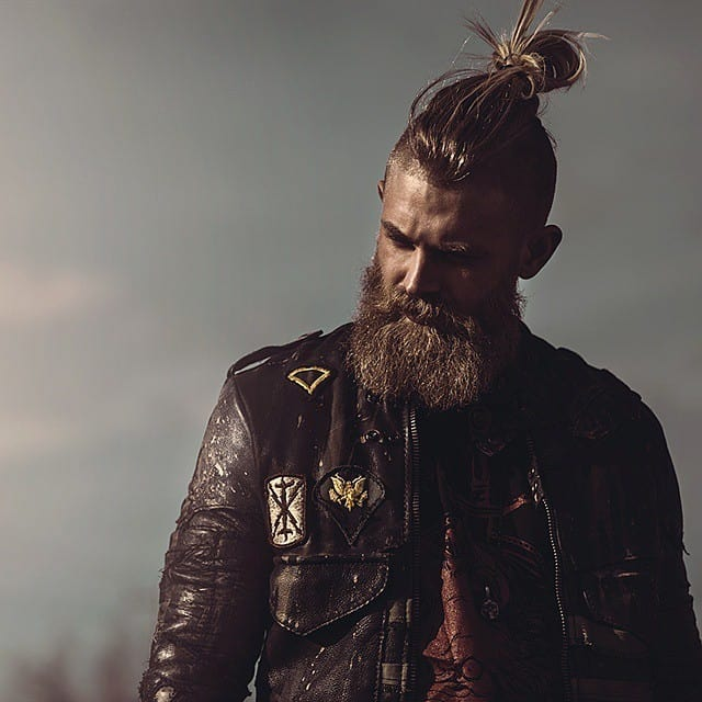 bearded man in a leather jacket with a mohawk tied in a bun