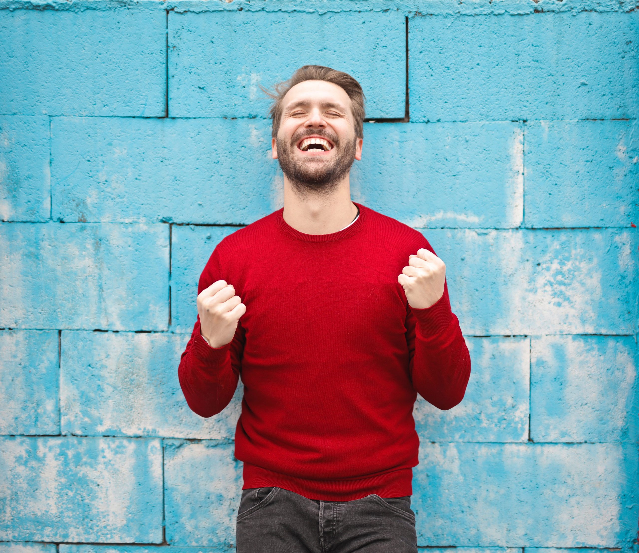 man in a long-sleeved red shirt laughing heartily while standing in front of a blue wall, coping strategies, healthy coping mechanisms