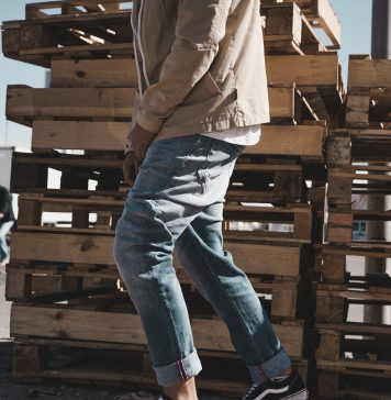 a man in a brown jacket, jeans and black sneakers standing near some wooden pallets