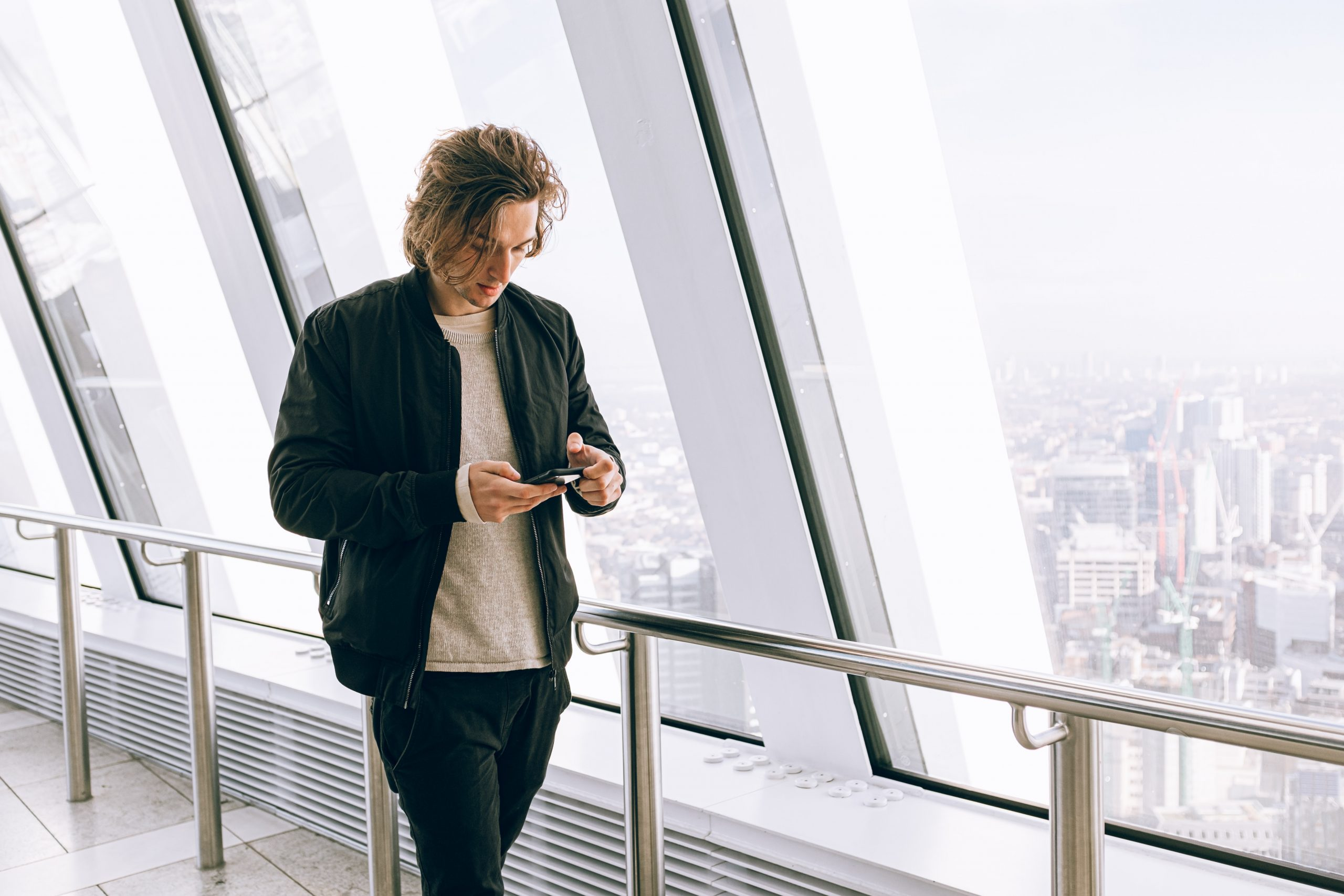 man walking along a walkway while looking at his phone, coping strategies, healthy coping mechanisms