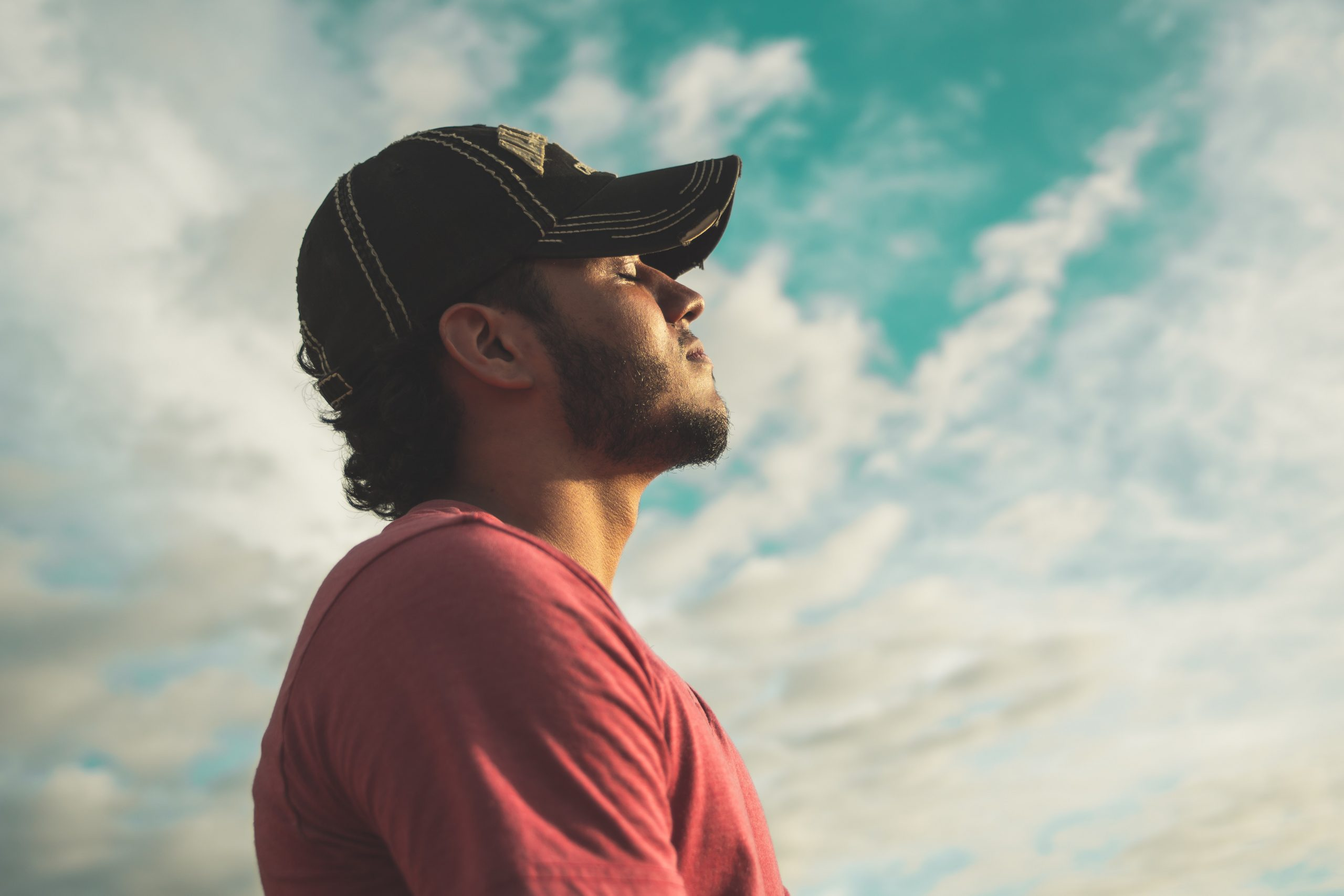 man wearing a red shirt and black cap facing the sky with his eyes closed, coping strategies, healthy coping mechanisms