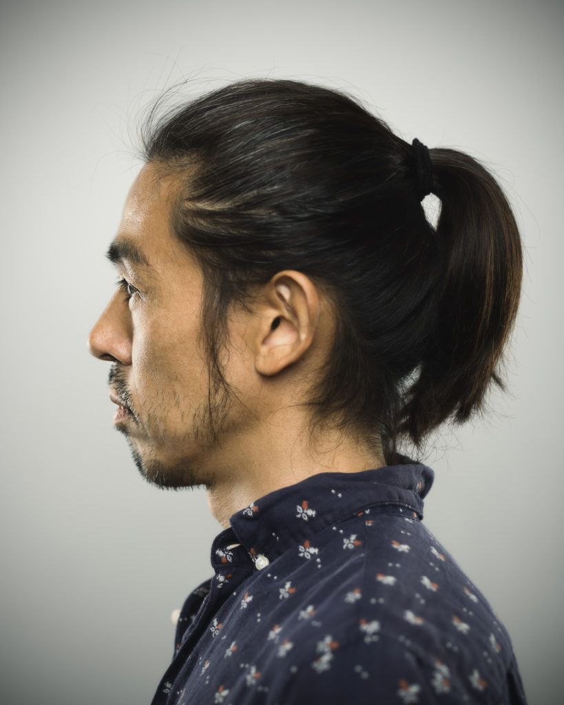 side profile of an asian man with a ponytail and wearing a navy patterned collared shirt