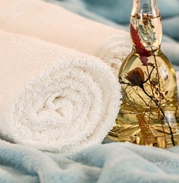 fresh towels with bottles of natural essential oils used in aromatherapy